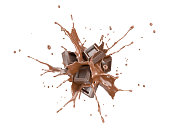 Chocolate blocks splashing into a liquid chocolate splash burst in the air.