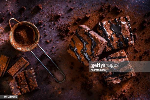 chocolate brownies on dark brown table - fudge stock photos and pictures