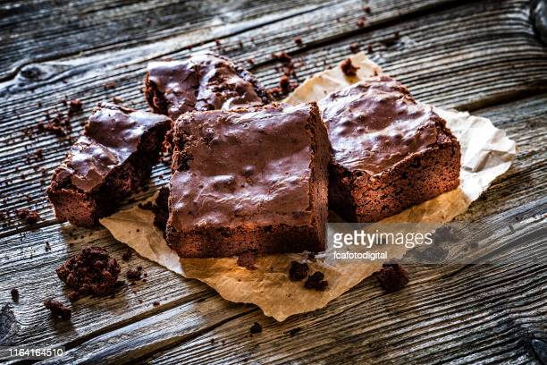 chocolate brownies on rustic wooden table - fudge stock pictures, royalty-free photos & images