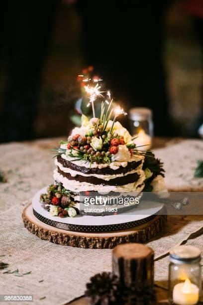 Schokoladenkuchen auf Tisch mit Blumen, Hochzeitstorte mit Rosen Schlagsahne