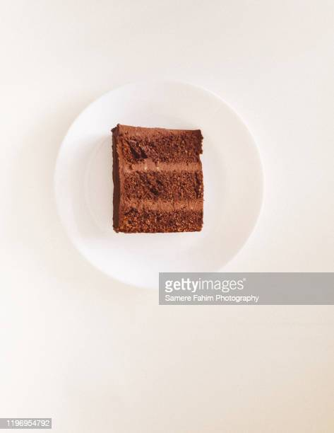 chocolate cake slice with avocado chocolate icing on a plate - cakestand stock pictures, royalty-free photos & images