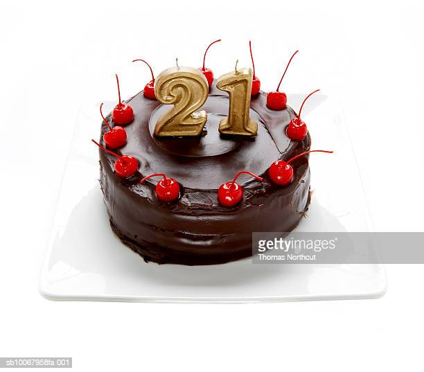Chocolate cake with cherries and candle reading '21' on white background