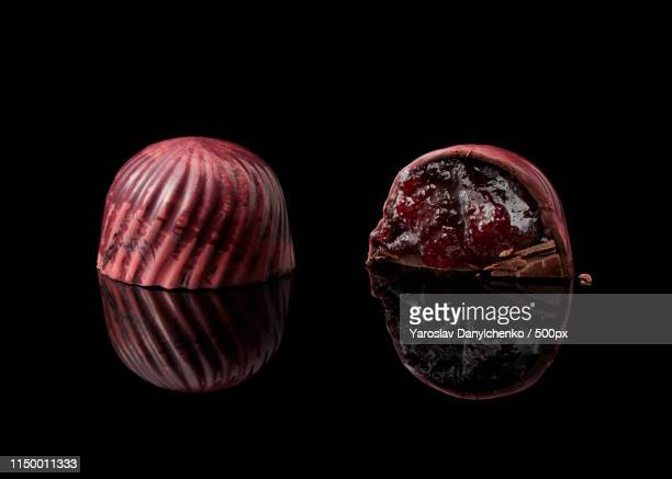 chocolate candy on black background - bittersweet berry stock photos and pictures