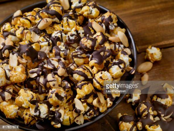 chocolate caramel popcorn with peanuts - popcorn stock pictures, royalty-free photos & images