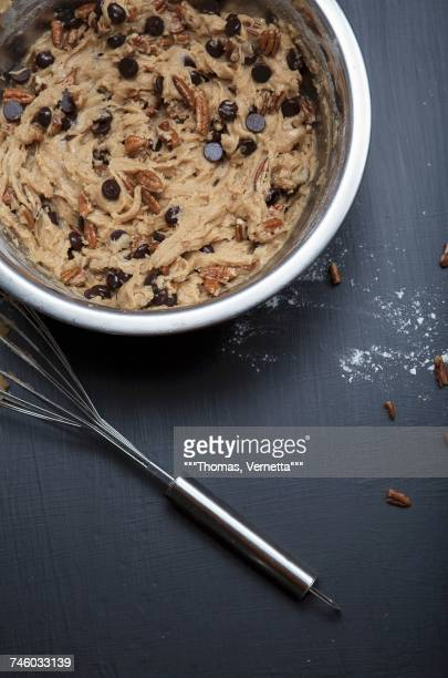 Chocolate chip cookie dough with pecan nuts in a mixing bowl