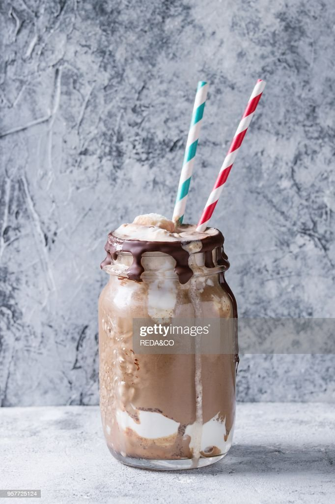 Chocolate coffee milkshake with ice cream scoop served in glass mason jar with retro cocktail tubes on gray texture background. Summer sweet drink : News Photo