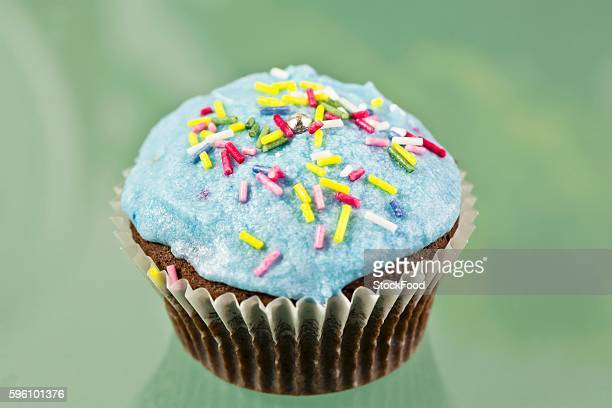 A chocolate cupcake decorated with blue buttercream icing and sugar strands