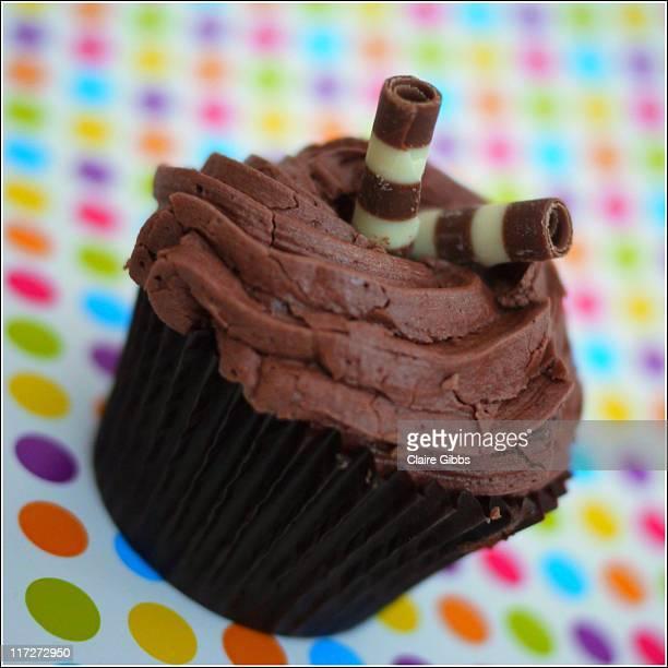 chocolate cupcake on spotty background. - chesterfield square stock-fotos und bilder