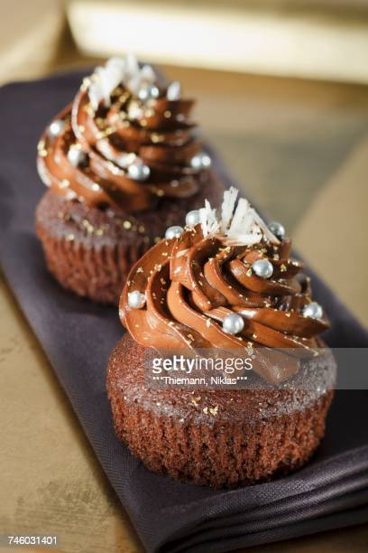 Chocolate cupcakes decorated with silver pearls and grated white chocolate