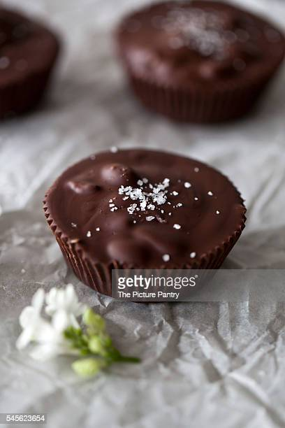 chocolate cups filled with date caramel with sea salt on a white paper and grey background - salted stock photos and pictures