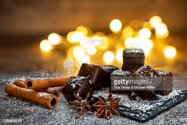 chocolate dominoes with powdered sugar, cinnamon sticks - christmas cake stock photos and pictures