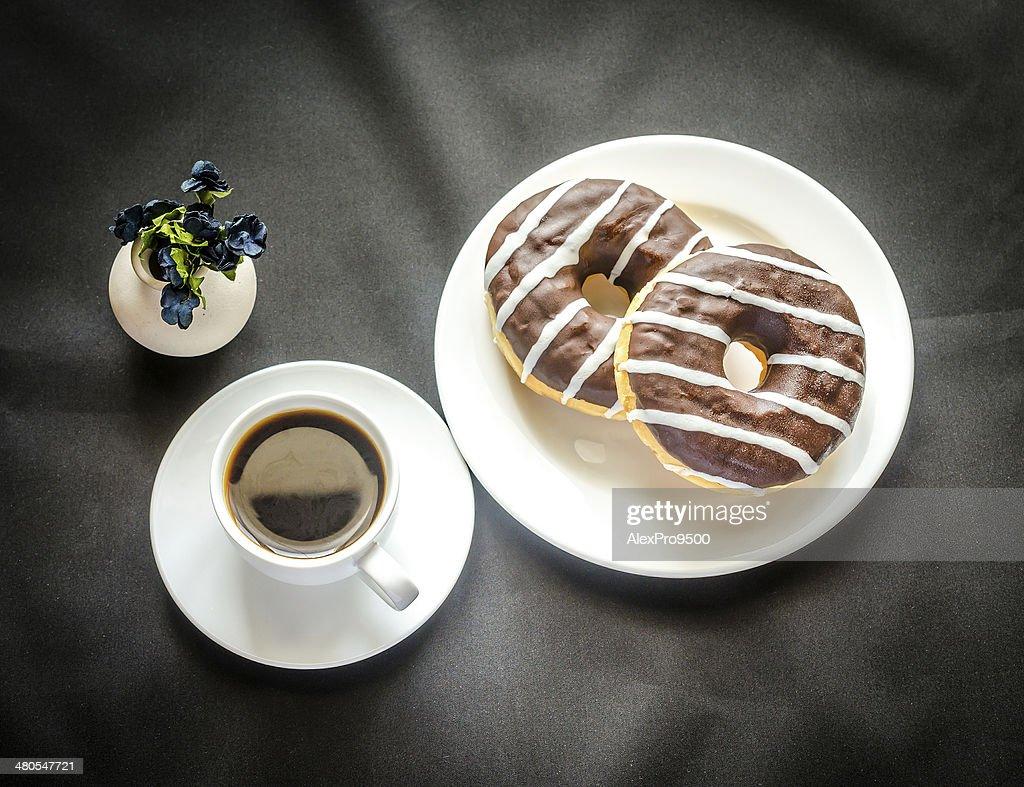 donuts de Chocolate com uma Xícara de Café : Foto de stock