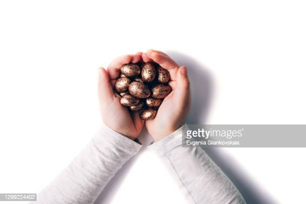 chocolate easter eggs in child's hands isolated on white background. - animal egg stock pictures, royalty-free photos & images