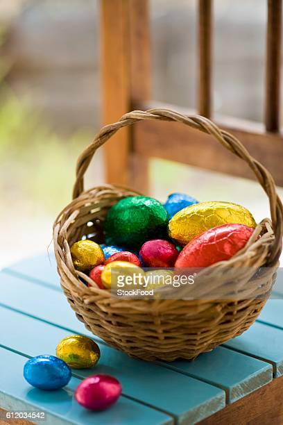 chocolate easter eggs in coloured foil in basket - イースターエッグのチョコレート ストックフォトと画像