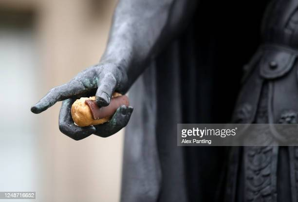 Chocolate eclair is seen in the hand of The Statue of King James II in Trafalgar Square on June 10, 2020 in London, England. As the British...