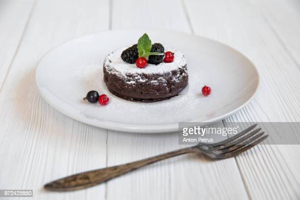 Chocolate fondant (lava cake) decorated with strawberries and powdered sugar
