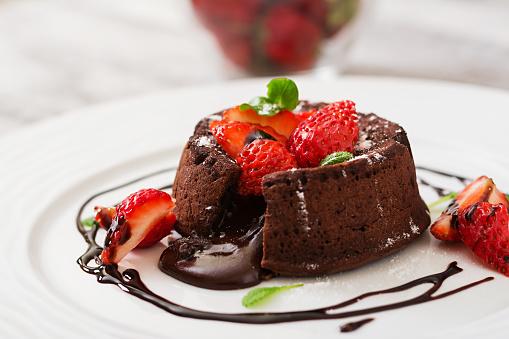 Chocolate fondant (cupcake) with strawberries and powdered sugar 541267186