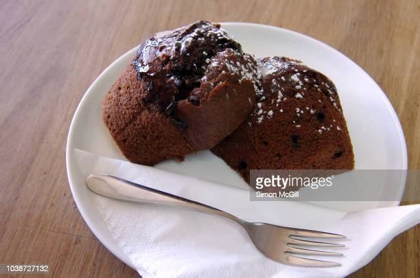 Chocolate fudge muffin cut in half and served on a plate with a paper napkin and cake fork