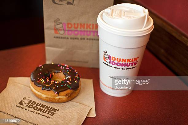 Chocolate glazed donut and a cup of coffee are arranged for a photograph at a Dunkin' Donuts Inc. Store in West Orange, New Jersey, U.S., on...