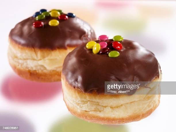Chocolate glazed doughnuts decorated with coloured chocolate beans
