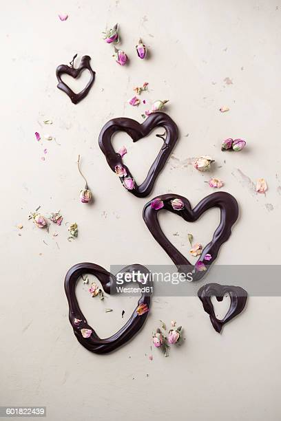 Chocolate hearts and dried rose blossom on light ground