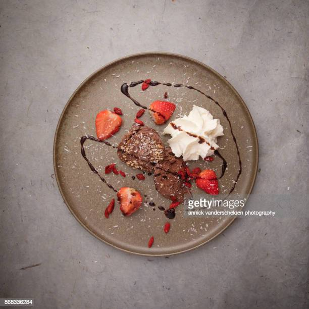 Chocolate ice cream, strawberries, whipped cream, goji  coconut and chcolate sauce.