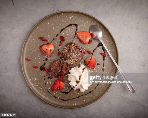 Chocolate ice cream, strawberries, whipped cream, goji  coconut and chcolate sauce.