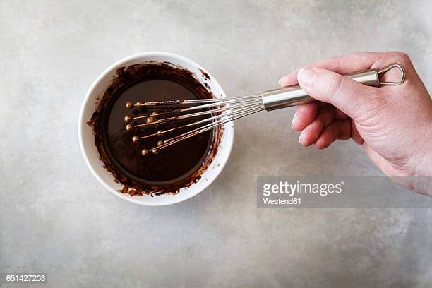 Chocolate icing, cocoa, cocoa butter and honey in bowl, stirrer
