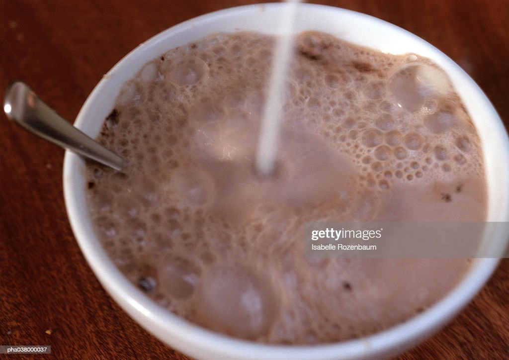Chocolate milk in bowl, with spoon, liquid being poured into bowl, blurred : Stockfoto
