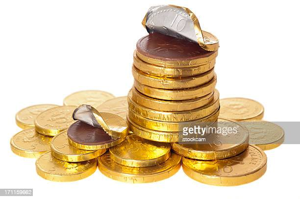 Chocolate money coins stacked on white