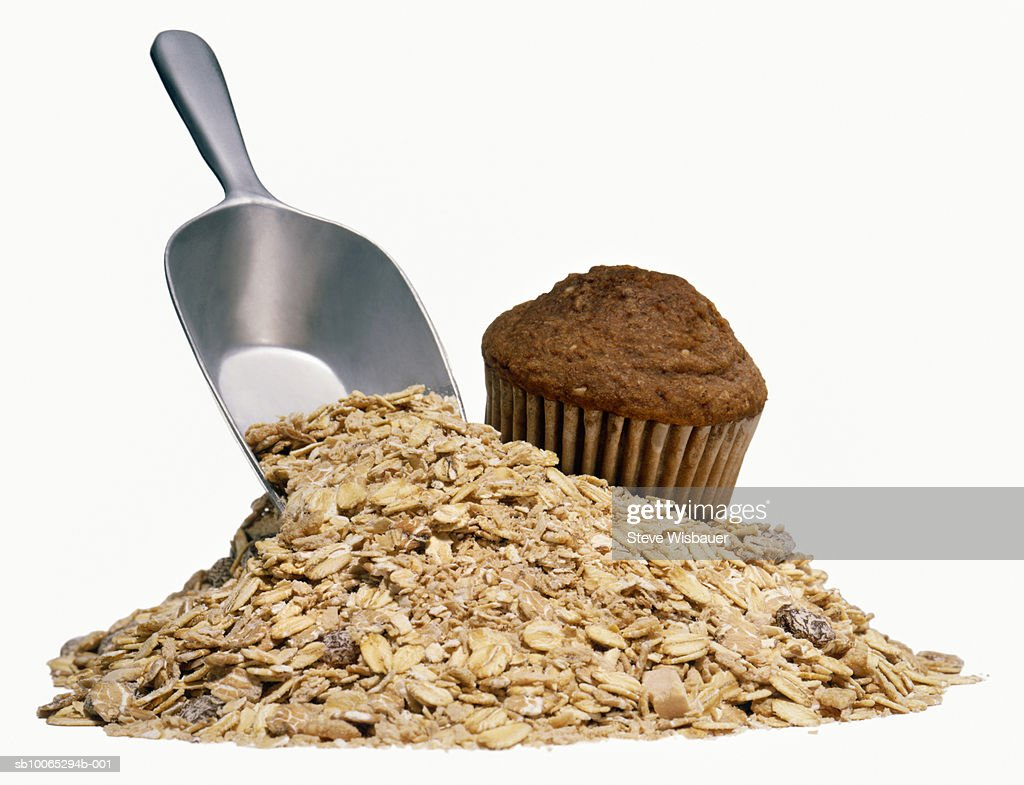 Chocolate muffin and pile of uncooked oatmeal with scoop, studio shot : Foto stock