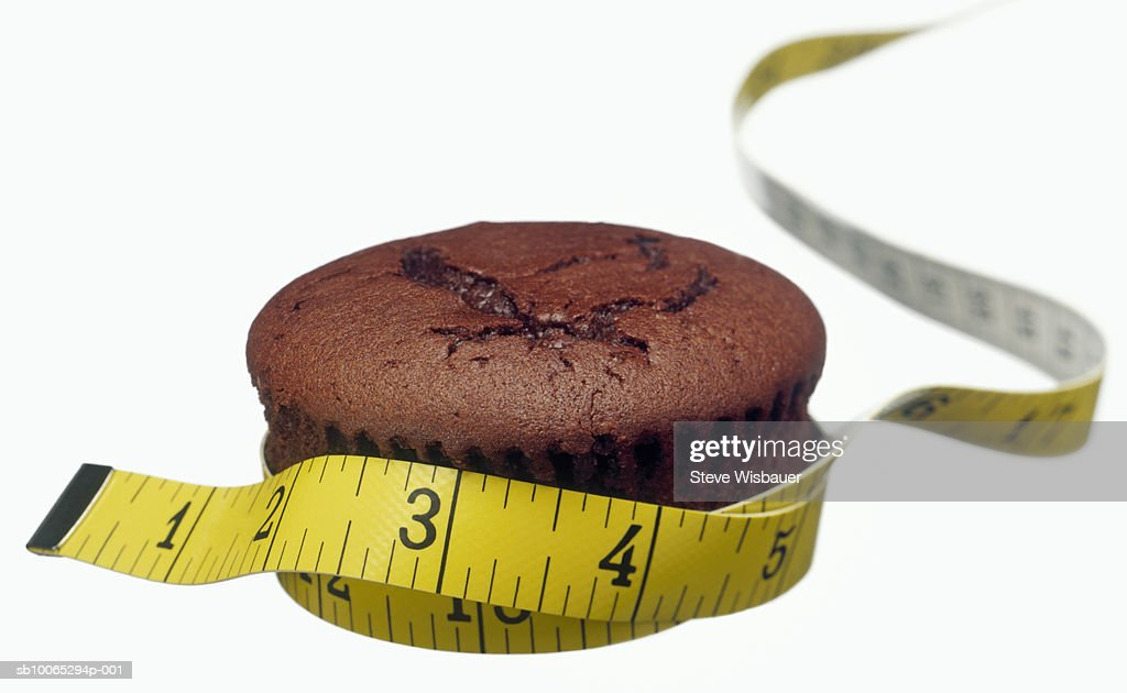 Chocolate muffin and tape measure, studio shot, close-up : Foto stock
