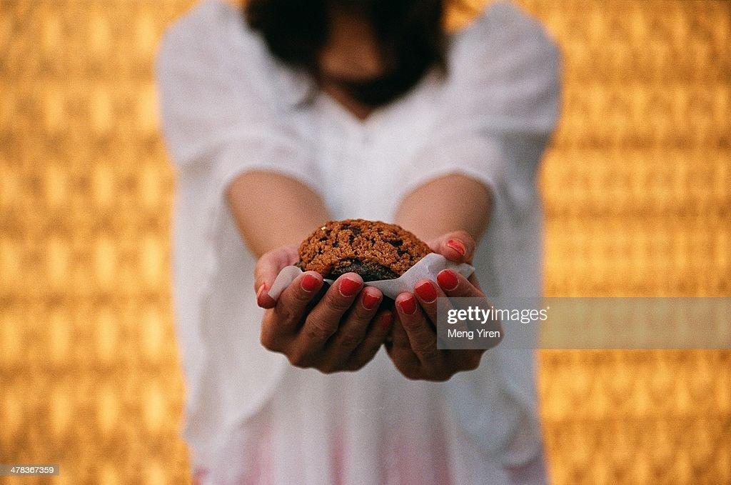 Chocolate muffin in girl's hand : Stock Photo