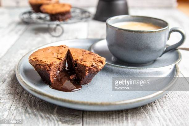 chocolate muffin with liquid chocolate on plate with coffee cup - coffee with chocolate stock pictures, royalty-free photos & images