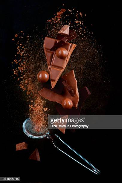 chocolate pieces and round chocolates balancing with cocoa powder explosion in motion. chocolate dust on a black background. action food photography. - dust dark stock photos and pictures