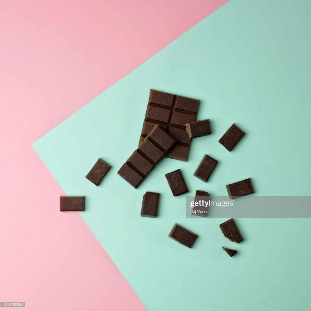Chocolate pieces on color block background : Stock Photo