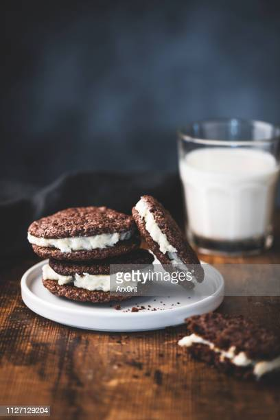 chocolate sandwich cookie and milk - chocolate photos stock pictures, royalty-free photos & images