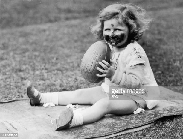 Circa 1930, A little girl makes a pig of herself with a large chocolate Easter egg.