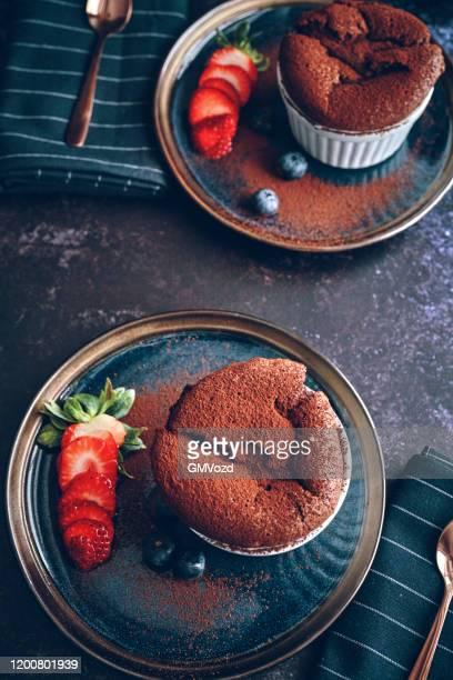 schokoladen-souffle serviert mit erdbeeren - soufflé stock-fotos und bilder