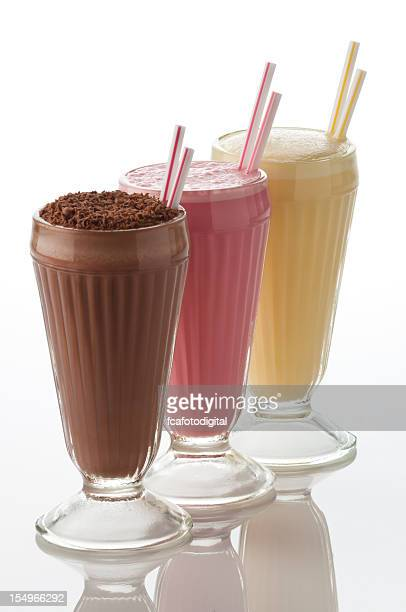 Chocolate, strawberry and vanilla milshake glasses in a row