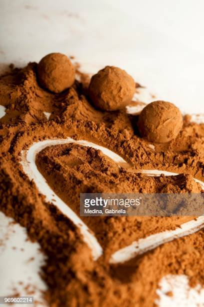 Chocolate truffles and a heart drawn in cacao