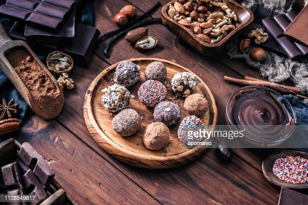 chocolate truffles and assorted dark chocolate with nuts on rustic old kitchen table - rum stock pictures, royalty-free photos & images