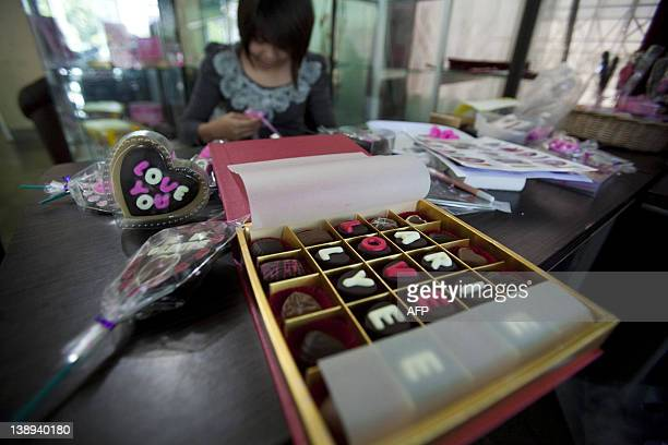 A chocolate vendor arranges packs of chocolates for Valentine's Day in Banda Aceh on February 14 2012 Many Indonesians celebrate Valentine's Day...