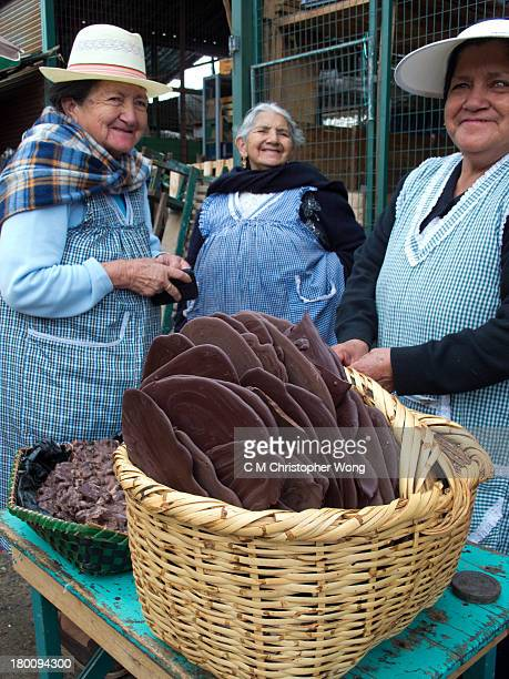 Chocolate vendor in the local wet market and her two customers just made a purchase. Cuenca, Ecuador, a country rich in cocoa production.