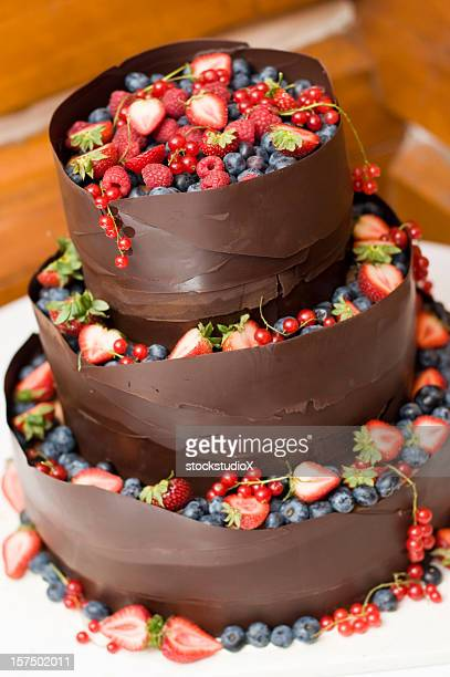 a chocolate wedding cake filled with assorted berries - fruit cake stock pictures, royalty-free photos & images