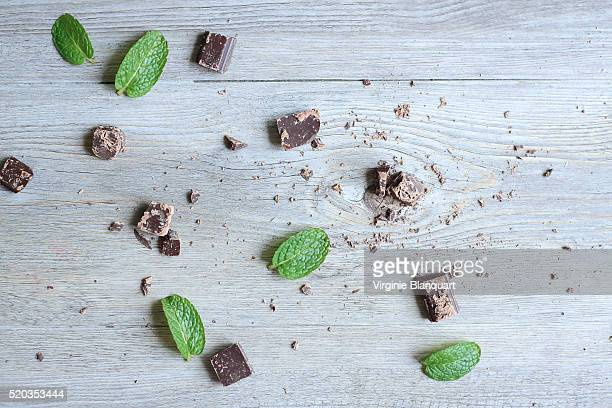 Chocolate with fresh mint leaves on wooden table