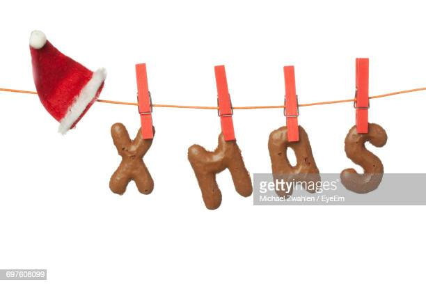 Chocolate Xmas Text With Santa Hat Hanging On Clothesline Against White Background