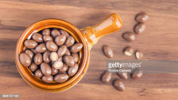 chocolate-coated almonds in glass bowl - chocolate dipped stock pictures, royalty-free photos & images