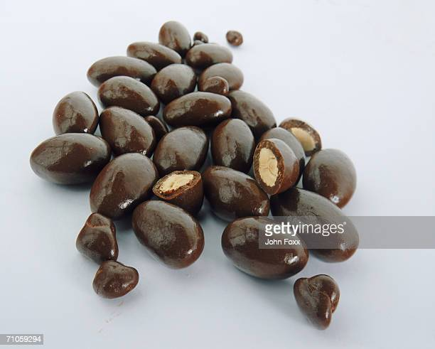 Chocolate-coated almonds on colored background, close-up