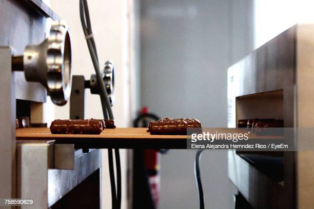 chocolates on conveyor belt in factory - chocolate factory stock photos and pictures